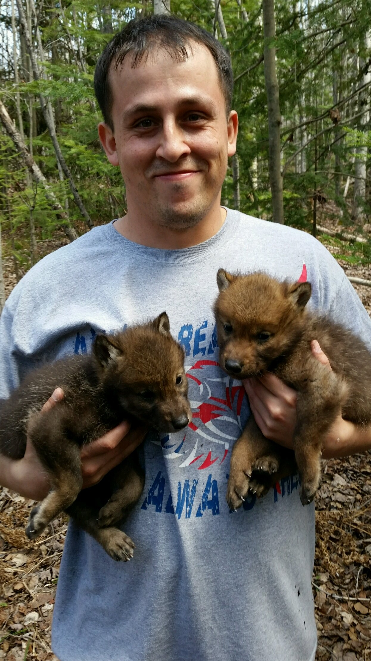 Jeremy St. Arnold holds two wolf pups