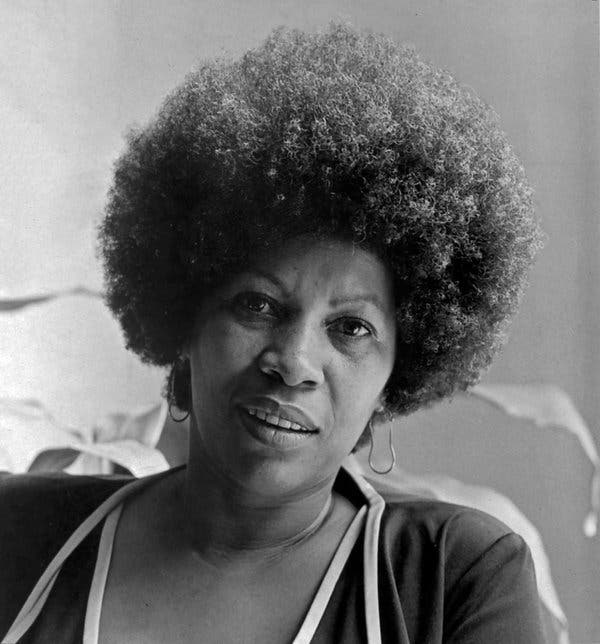 Toni Morrison, in a black and white picture from 1974, wears a large Afro and hoop earrings.