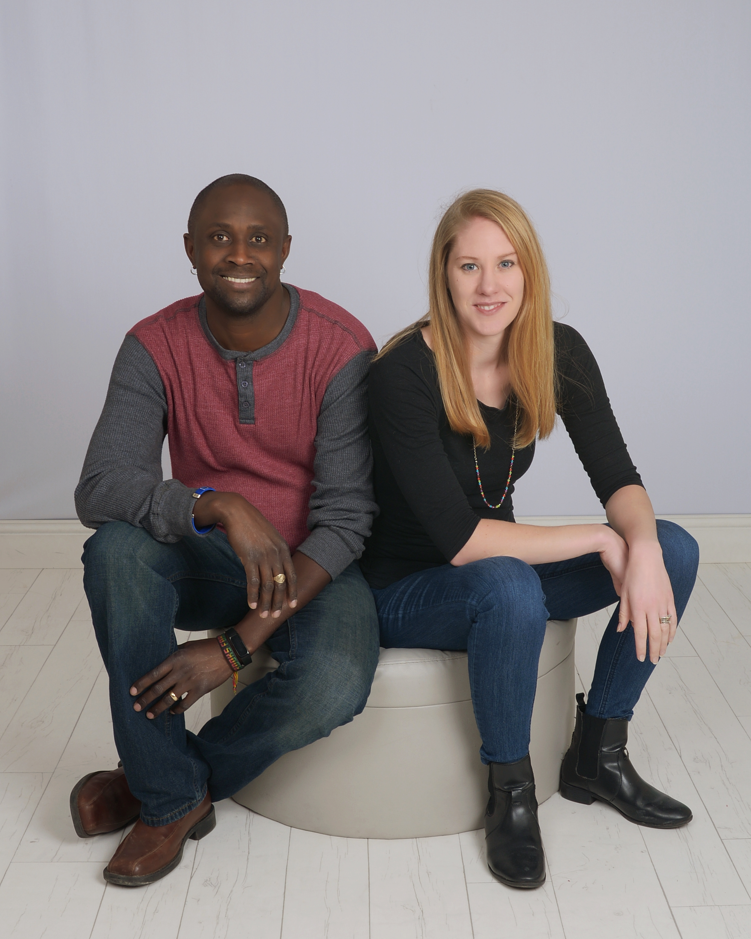 Baptiste Paul, a dark-skinned man wearing a gray and maroon shirt, and Miranda Paul, a light-skinned woman with long blonde hair, sit together and smile.
