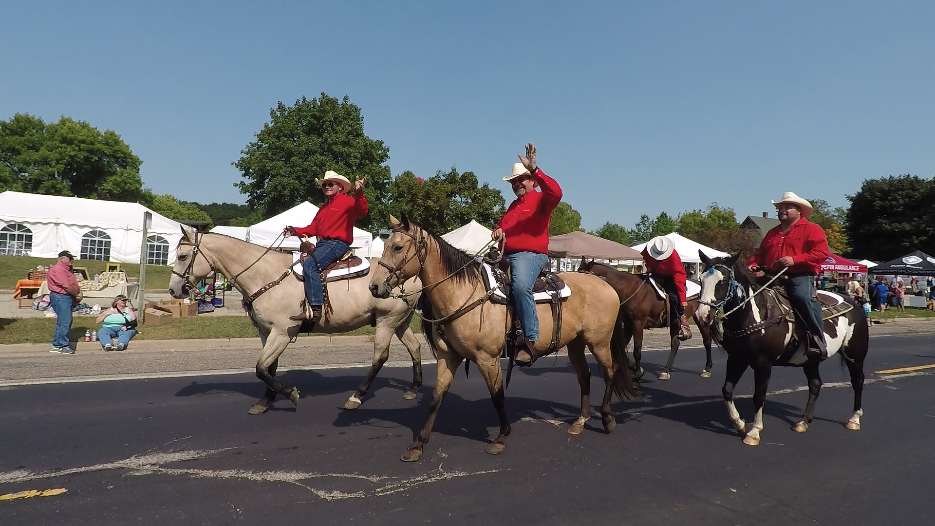 Cowboys in red shirts wave from horseback as they ride down a small-town street in a parade