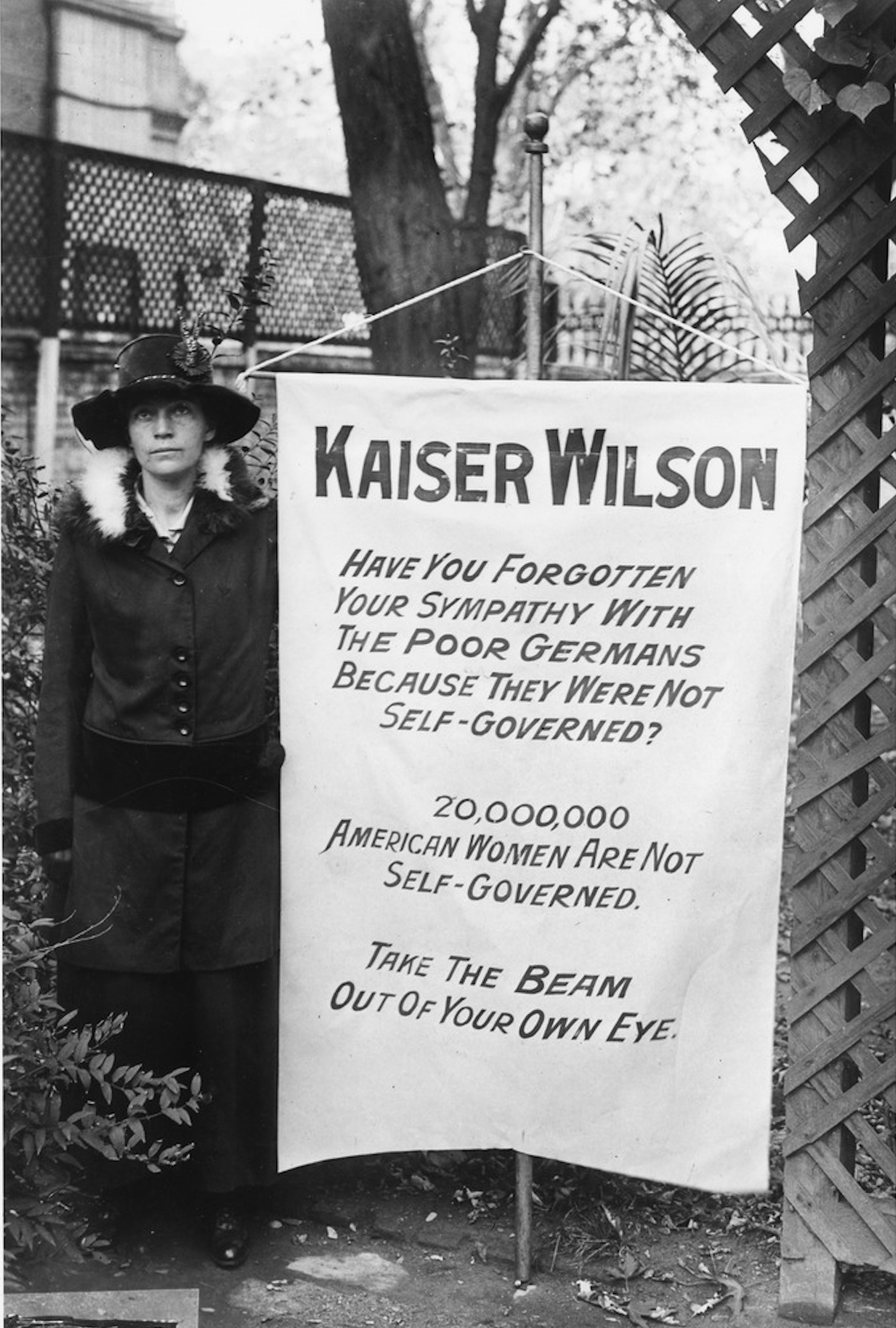 "A woman stands next to a banner referring to the president as ""Kaiser Wilson"""