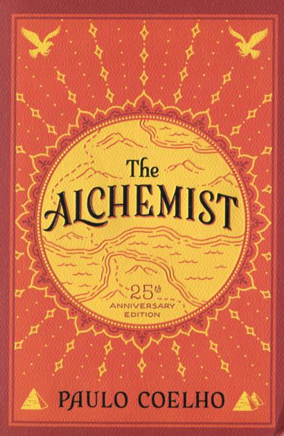 Bright orange and yellow cover of The Alchemist, with patterns resembling mountains on a map