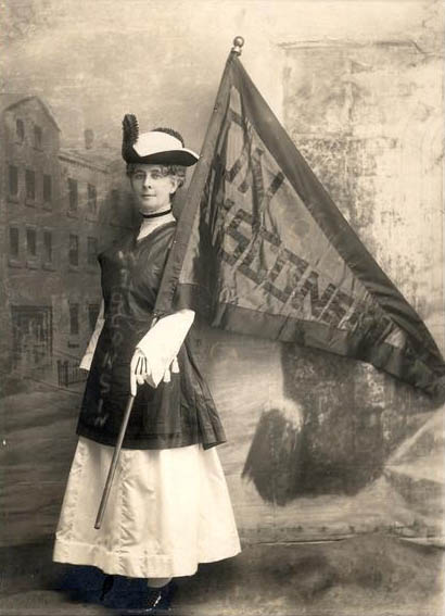 In a vintage photo from the early 1900s, a woman holds an On Wisconsin flag