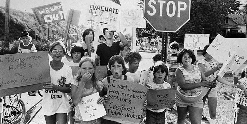 Young children hold up signs protesting environmental destruction