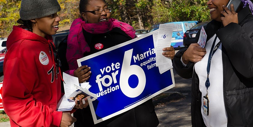 African-American women hold political signs.