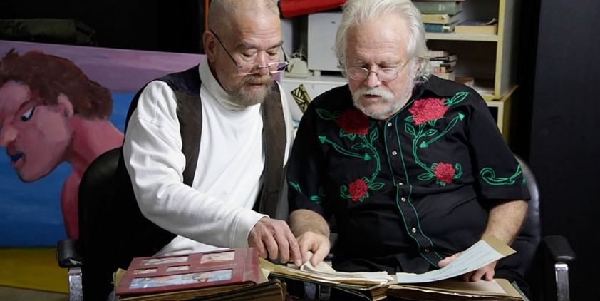 Two older men review a photo book.