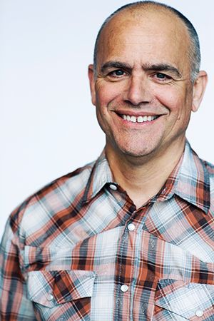 Author Michael Perry smiles and wears a plaid shirt.