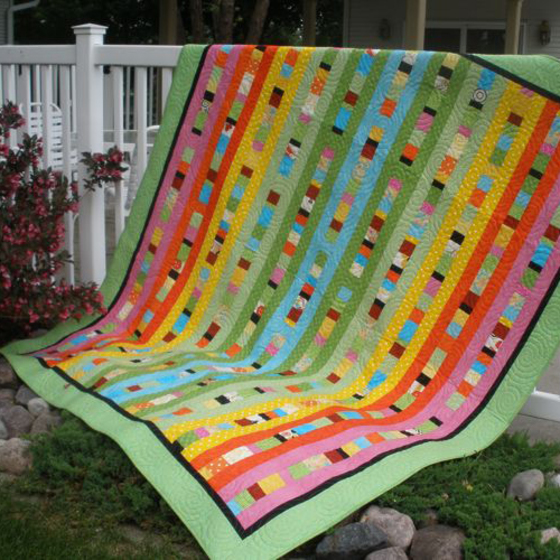 A brightly colored strip quilt is displayed before donation to Quilt to Give