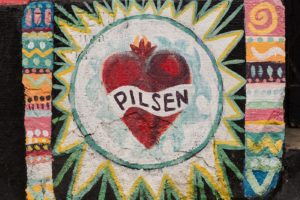 """A colorful painted mural on concrete features a heart with a banner reading """"PILSEN."""""""
