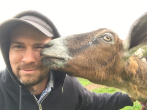 A goat licks Colin Crowley's face.
