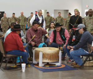 "Men sing and play a ""big drum"" surrounded by military veterans."