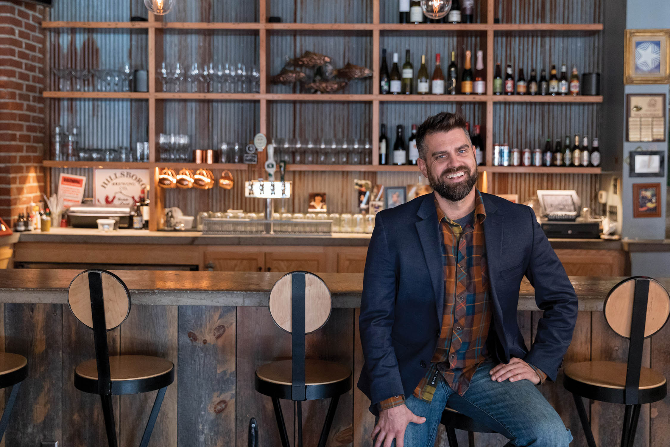 Luke Zahm sits at the bar in his restaurant, Driftless Cafe.