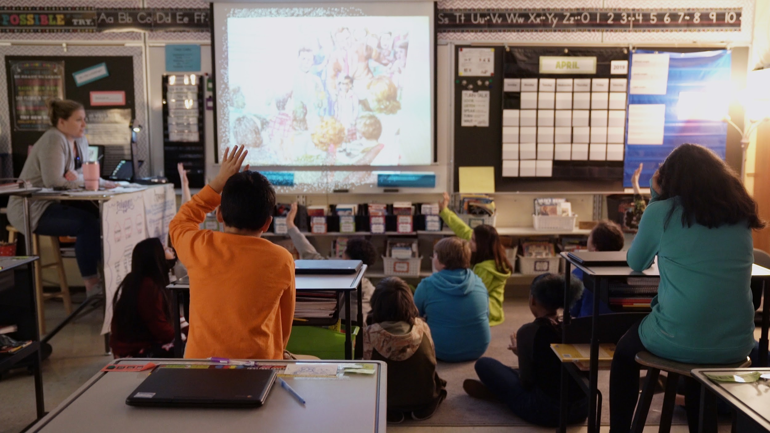 Students raise their hands in a Green Bay classroom.