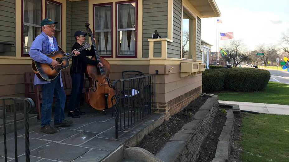 Man playing guitar and woman playing upright base on front porch