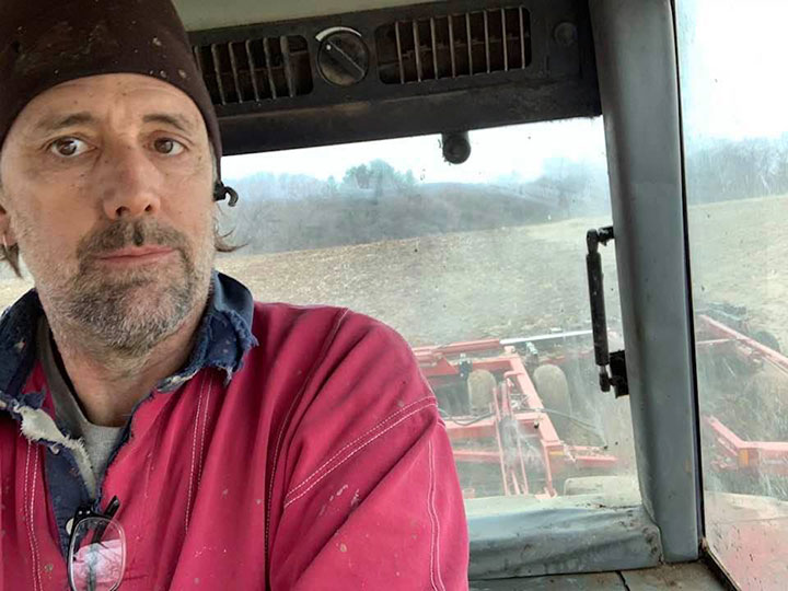 Farmer in tractor with field behind him