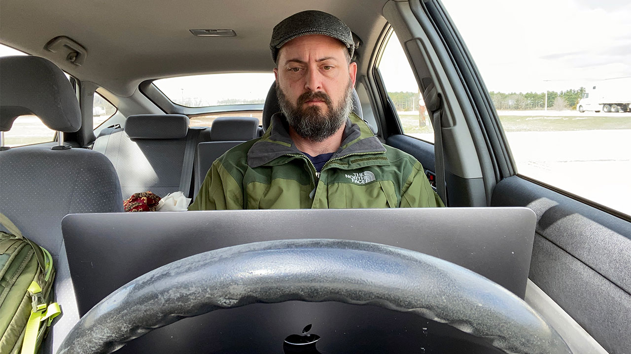 Man sitting behind steering wheel of car with an open laptop computer