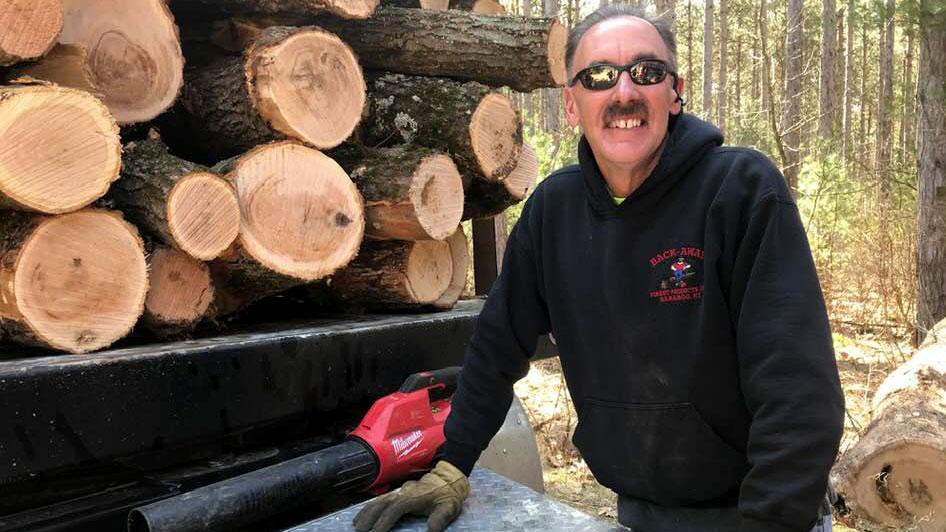 Man standing next to cut logs