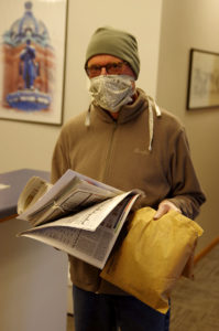 Man wearing face mask and hat and holding newspapers