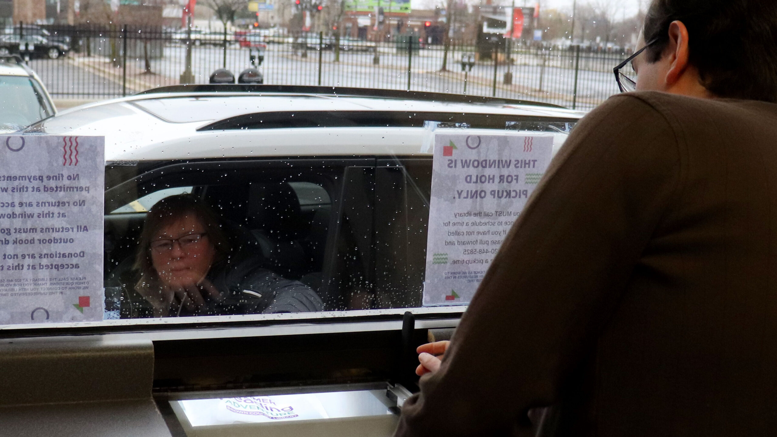 Women in car at a library's drive-up window