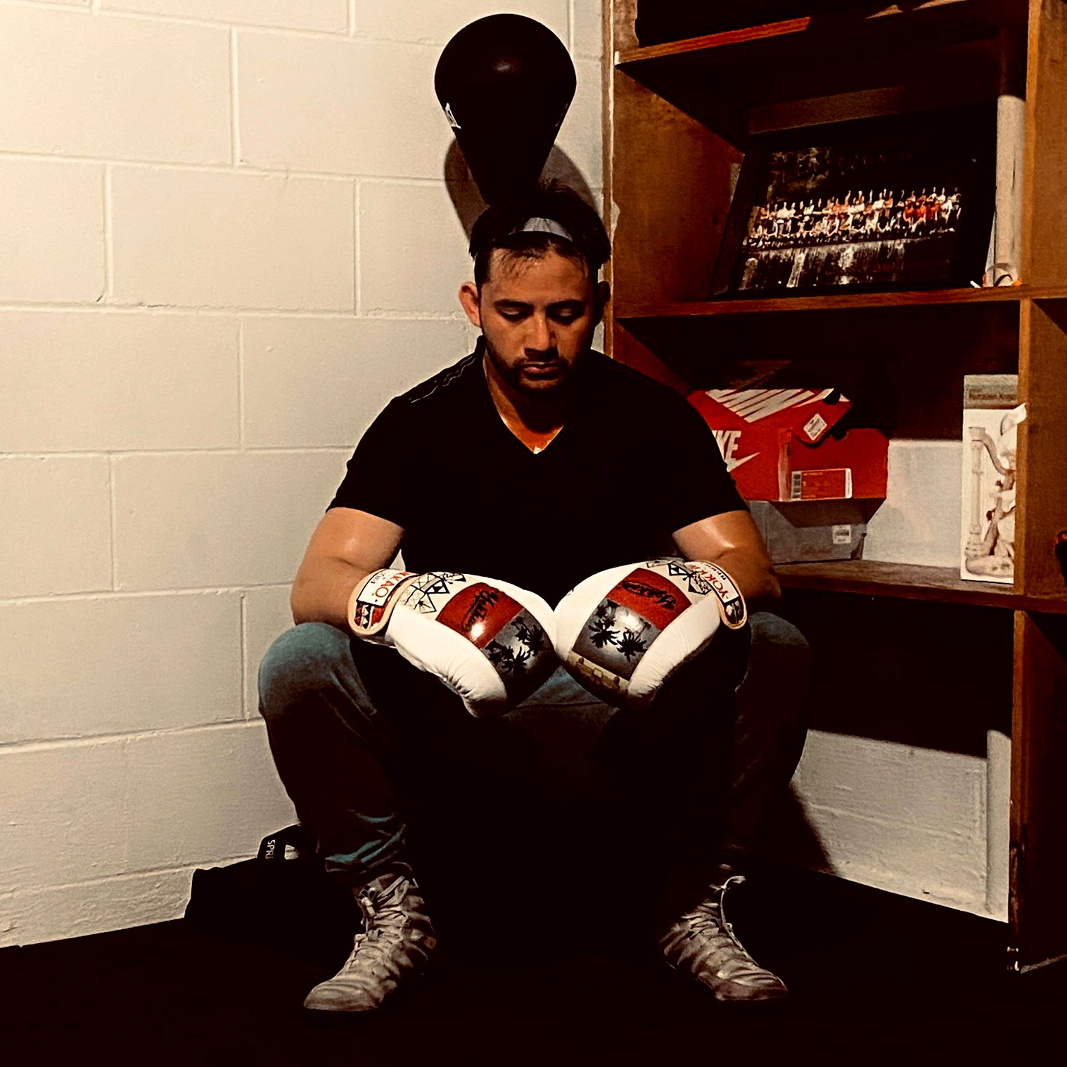 Man sitting in a corner and wearing boxing gloves
