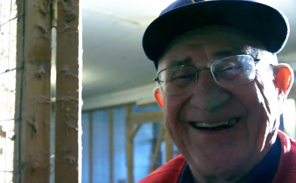 Smiling man wearing hat and glasses.