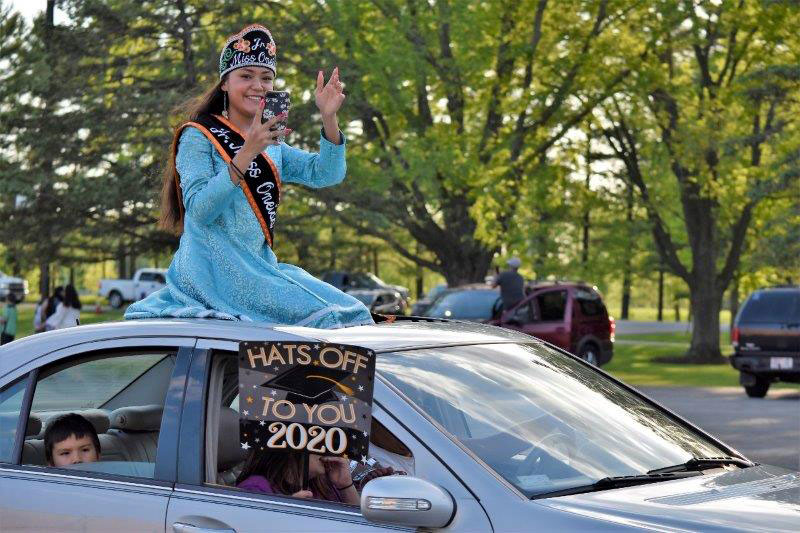 Graduating senior sitting on top of a car in a parade