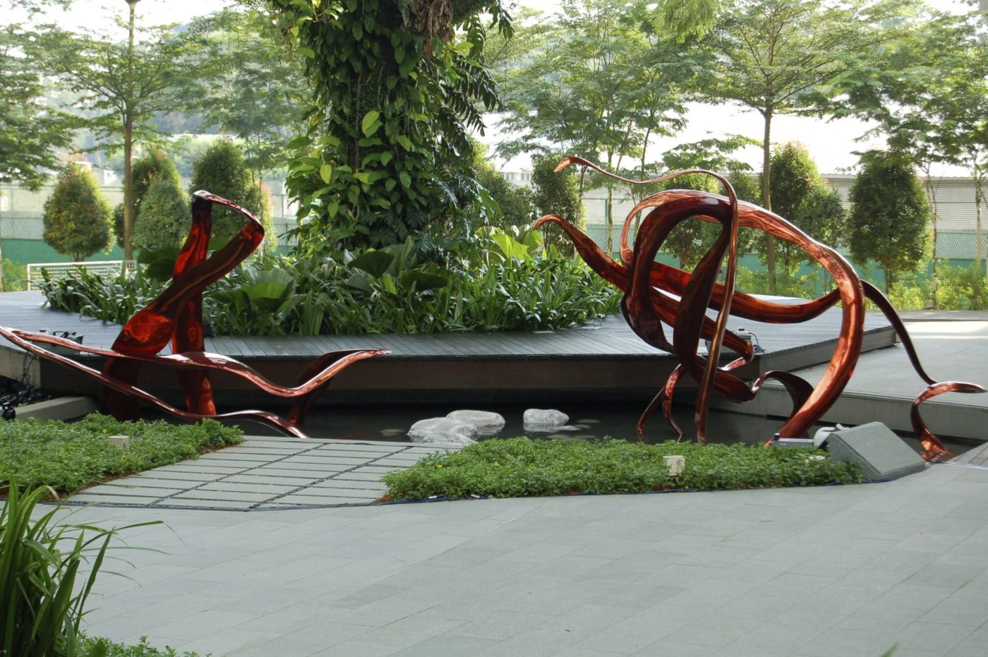 """""""I chose to make a sculpture of the SARS protease because Biopolis Scientists were so excited about their contributions to developing drug candidates for SARS in 2002-2003, a deadly Coronavirus. I chose to create the sculpture in a brilliant red patina over the bronze which adds a flash of color and movement to the plaza."""""""