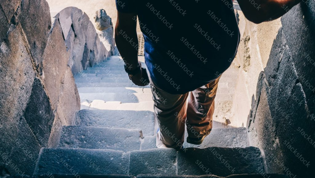 Man walking down the steps of Prambanan Temple Compounds,Indonesia