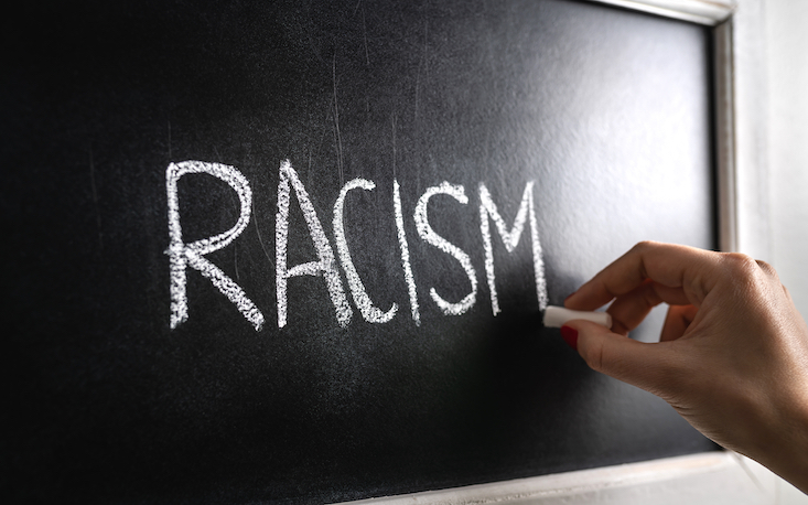 """Photo of chalkboard with text """"racism"""". Anti-racism in the classroom."""