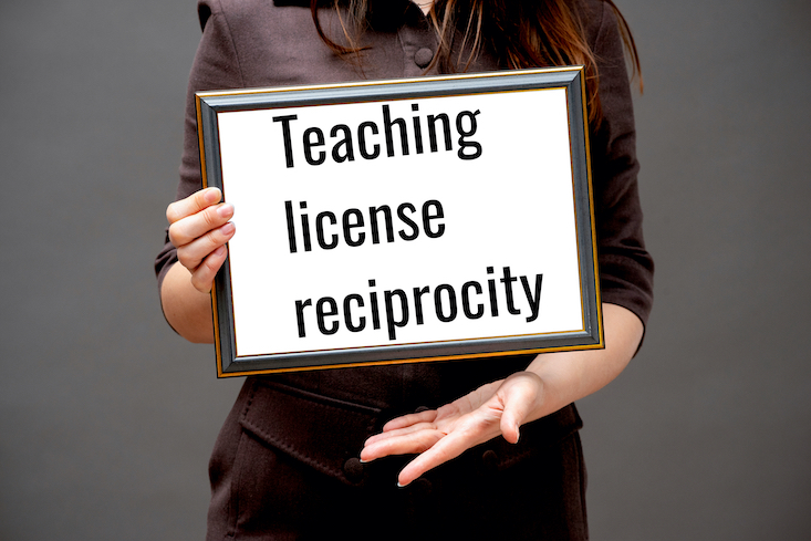 "Photo of woman holding up certificate that says ""Teaching license reciprocity""."