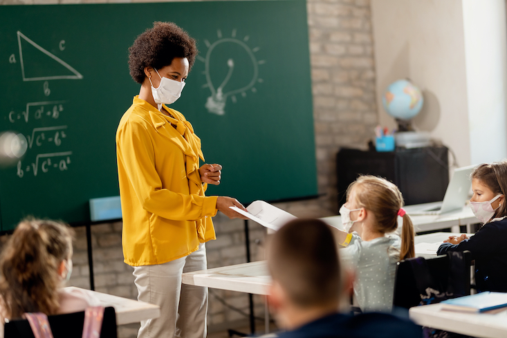 Photo of a teacher with mask on in classroom.