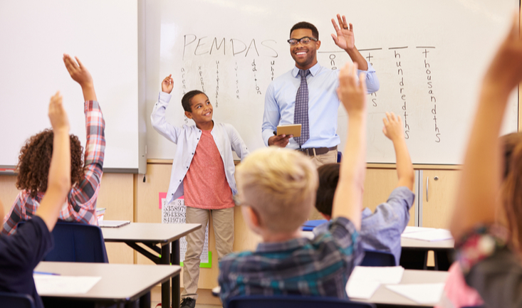 male teacher standing in front of an enthusiastic class of young students