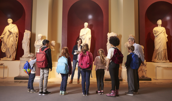 teacher in front of students at a museum standing in front of statues of ancient philosophers