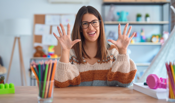 woman sitting at a desk holding 10 fingers up