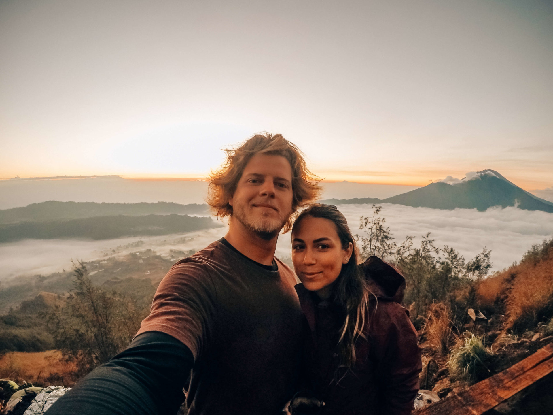 A couple taking a selfie ontop of a volcano.