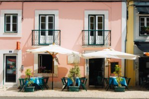 A cafe painted pink with tables outside.